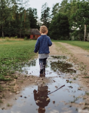 boy walking in puddle